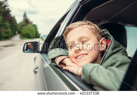 stock-photo-dreaming-boy-look-out-from-the-car-window-421337338.jpg